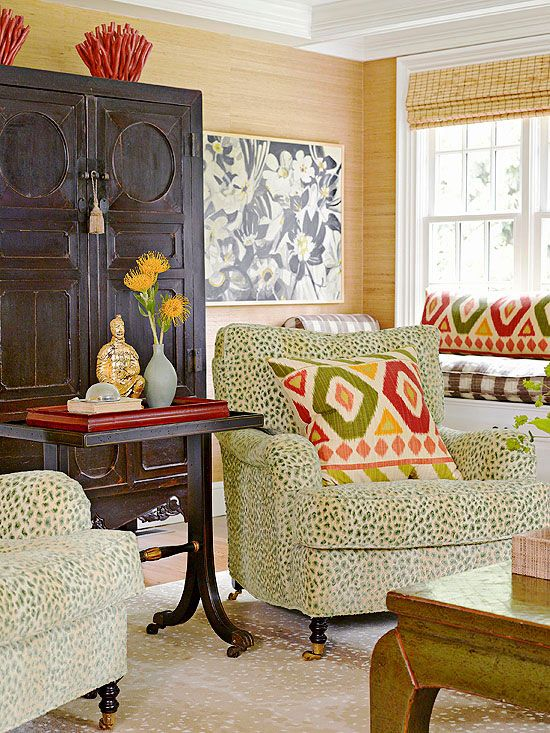 """The entire combination here--from the """"grassy"""" wallpaper, to the matchstick blinds, to the bold Ikat pillow fabric, to the leopard-spot upholstery, it all CLICKS! The Oriental cabinet leads the eye upward. This is color at its best! LOVE that green and red!"""