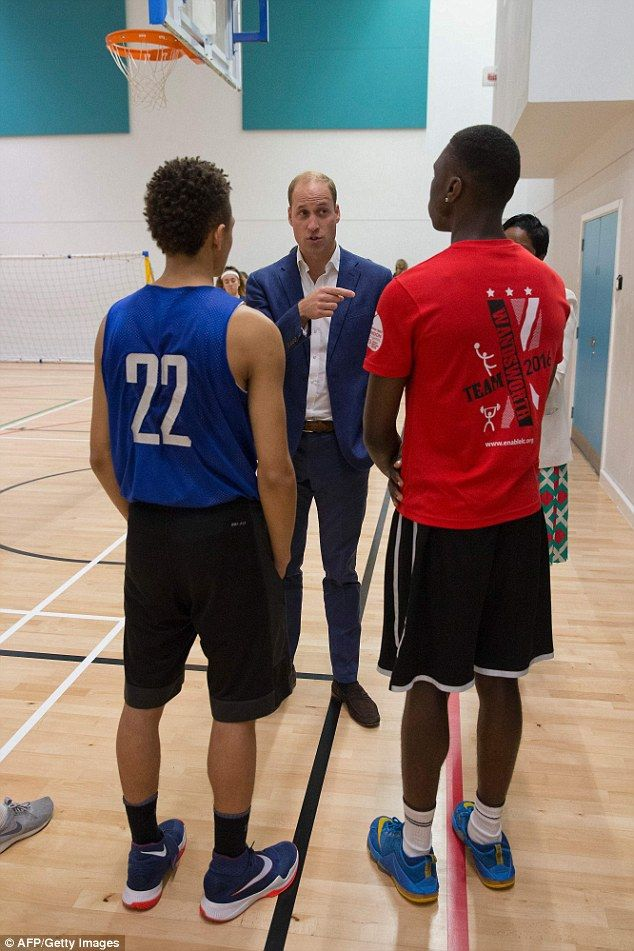 Prince William meets the basketball team on a visit to Caius House