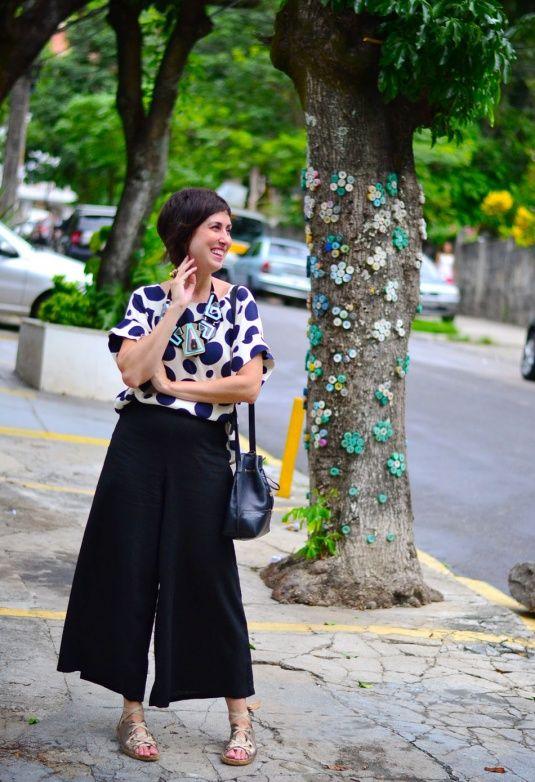 blusa de mangas curtas branca com bolas azuis marinho, calça pantalona curta preta, sandália de amarrar dourada e solado de corda, colar gigante geométrico preto, rosa e azul