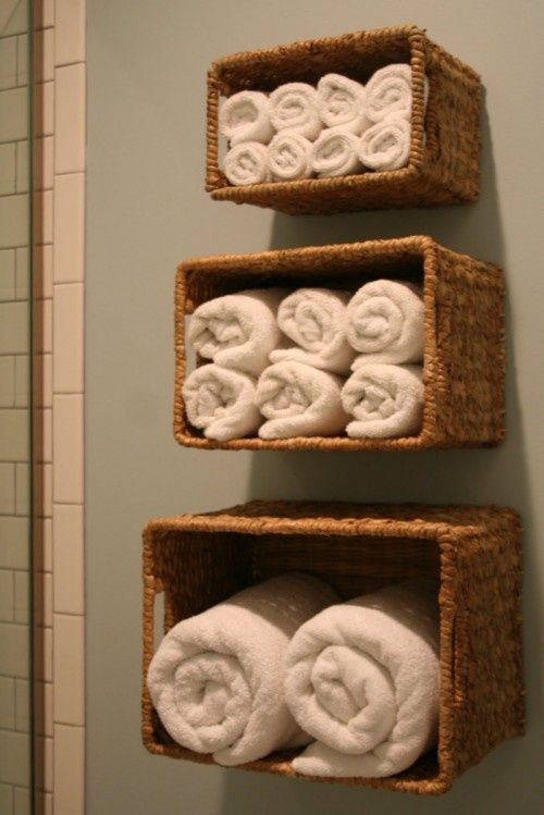 Attach wicker baskets to the wall and fill with rolled up fluffy towels