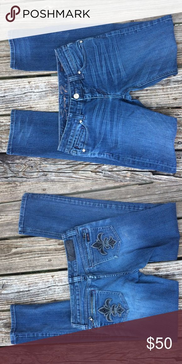 7 for All Mankind Slim Jeans - Flur De Lis Pockets Whisker Jeans in a medium wash with shuddering. Back pockets are detailed with flur de lis - embroidered and lightly beaded. Back pockets zip closed. No rips, tears, or stains. In great preowned condition. Light signs of wear. 7 For All Mankind Jeans