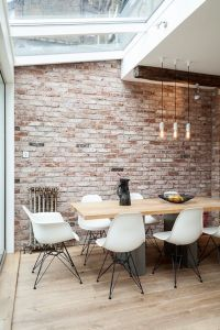 Open plan kitchen and dining area, modern dining table, pendant lighting, exposed brick wall, white chairs