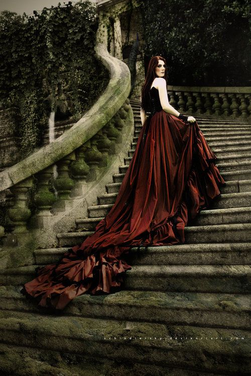 Fantasy image of a dark-haired woman in a red evening gown with a long train, on mossy stone stairs covered in vines.