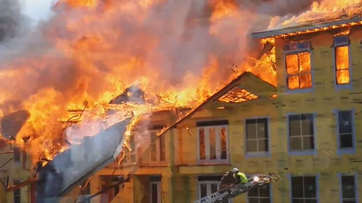 Man dangles from balcony in daring fire rescue caught on camera