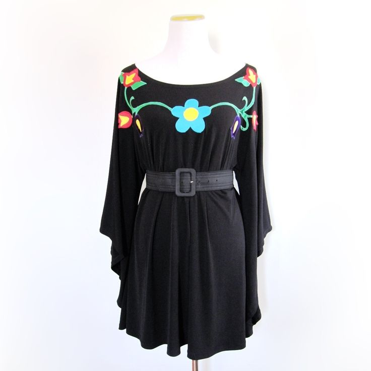 This top was designed by Tammy Beauvais (Mohawk Nation) and features a woodlands floral appliqué design. .