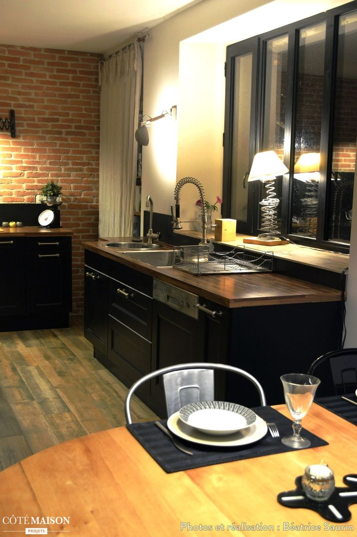 Cuisine stylée esprit industriel avec mur en briques, finitions alu et fenêtres type atelier.