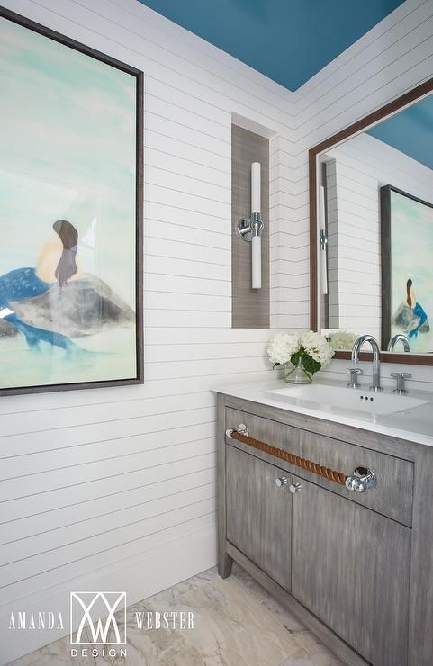 Stunning beach style cottage powder room boasts an eye-catching gray wash washstand complemented with a polished nickel knobs, a rope towel bar, and a white quartz countertop finished with a large undermount sink and polished nickel gooseneck faucet.