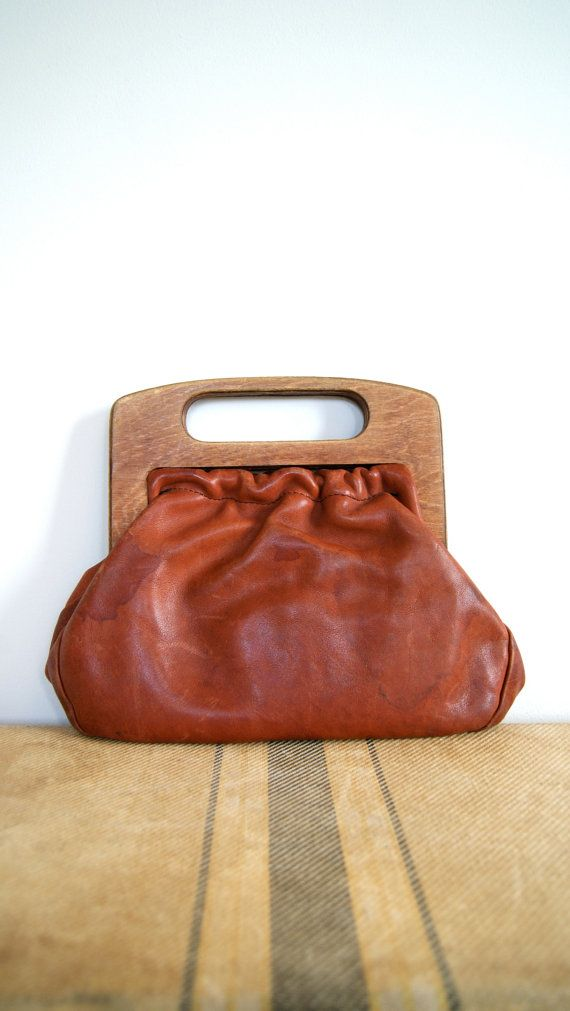 Gorgeous 60's era handbag made of leather with wooden handles. Lined in a soft plaid flannel. This leather is definitely distressed. Lots of marks and some scuffs. Personally, I think that makes it even better. (Measurements when flat: 11x 9'').