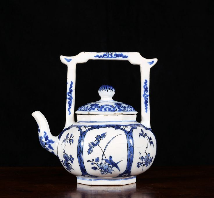 A Delft Hoppestyn Teapot and cover, Het Moriaenshooft (The Moor's Head) Factory 1679 - 1686 IW 4 in blue for Jacob Wemmersz Hoppesteyn 1679-86 Height : 18.6 cm  Width : 17.2 cm   The hexagonal body with high yoke handle decorated in blue with black outlines with panels of flowers after Chinese 'transitional' porcelain. The domed cover with globular finial. The form is taken from a Chinese Yixing redware teapot.   Jeroen P.M. Hartgers