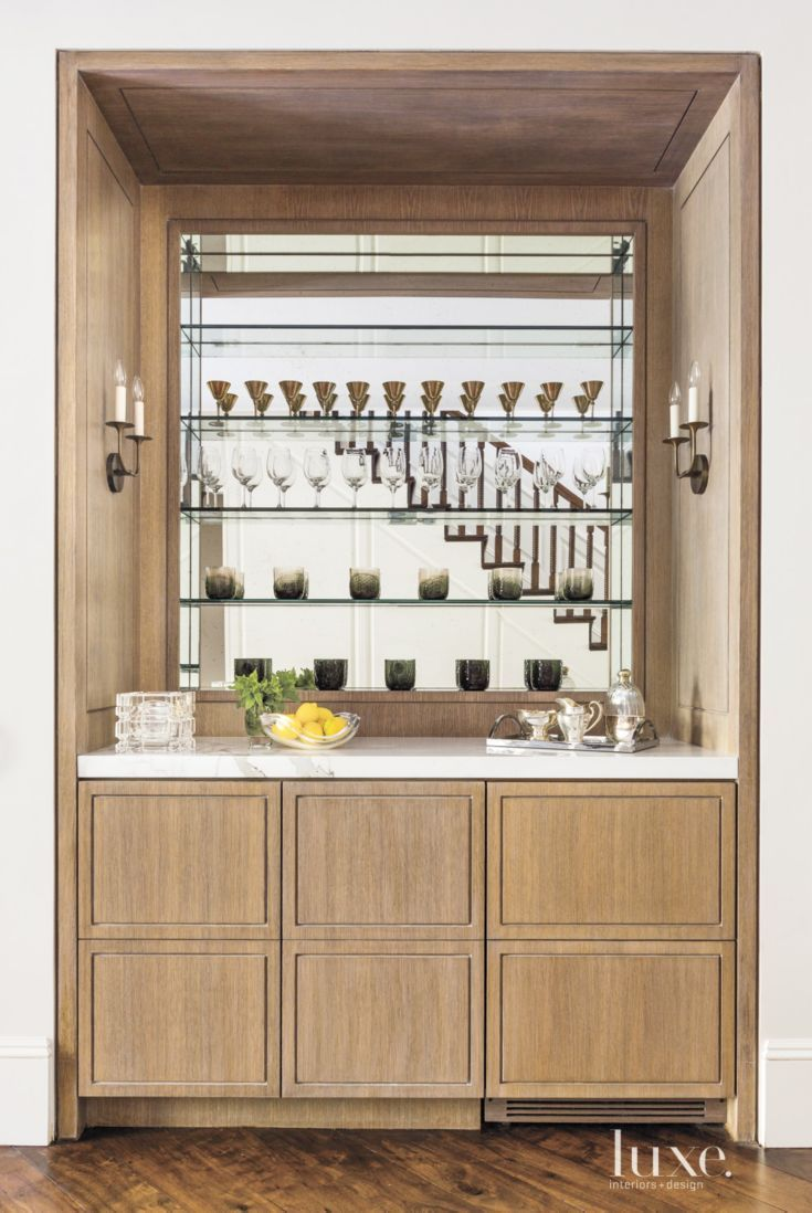In the hallway between the living room and library, a custom-designed bar by Studio Frazar casts a warm glow thanks to a combination of fumed white oak, an antique mirror, and sconces by Remains Lighting. The polished statuary marble on the countertop lends both beauty and durability.