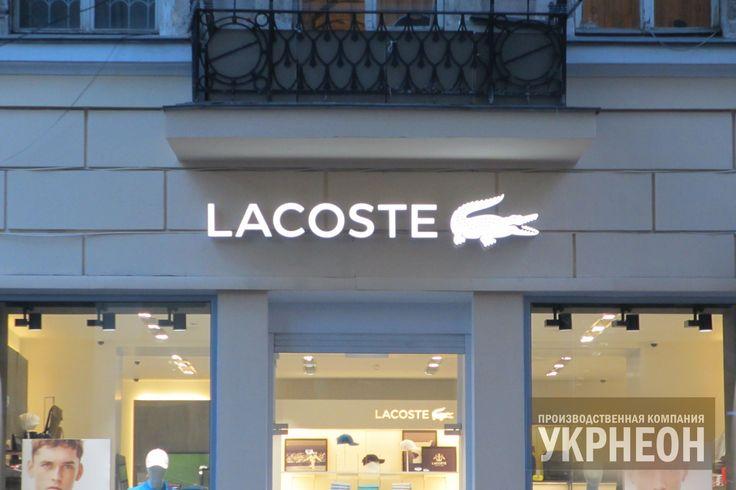 Фасадная вывеска для магазина LACOSTE. объемные буквы с внутренней светодиодной подсветкой и логотип в виде лайтбокса подчеркивают стиль и индивидуальность магазина, а двухсторонний флажок является прекрасным дополнением к вывеске.