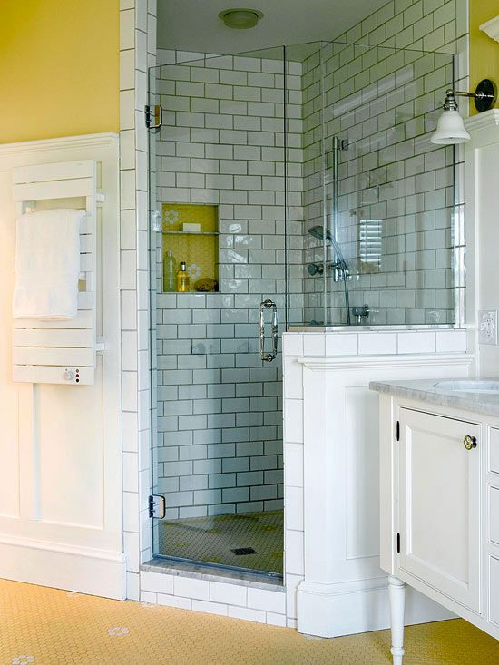Corner showers can be a great way to make the most of the space in a small bath. This shower adds vintage charm to a new bathroom, thanks to subway tiles with dark grout lines on the walls and hexagonal mosaic tile on the floor. A partial wall enclosure subtly separates the shower from the adjacent vanity area.  /
