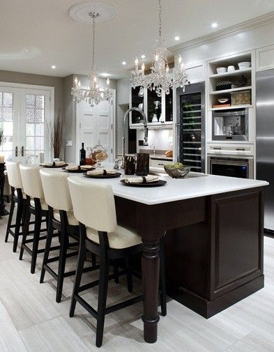 This is my sort of kitchen. Breakfast bar for guests to sit and chat over wines whilst I cook up a meal for all to enjoy. Very social. Very glamourous with the chandeliers. Love it.