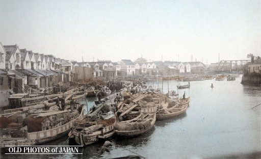 Boats are docked in front of a long row of warehouses in Koamicho in Tokyo's mercantile quarter of Nihonbashi. Ogawa was looking towards Yoroibashi, a steel bridge built in 1873 (Meiji 6), which can be seen in the far right of the image.