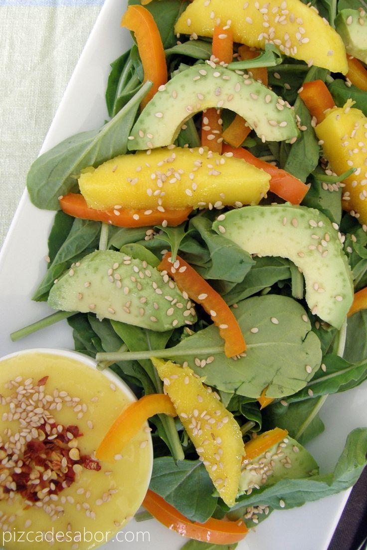 Una rica ensalada de arugúgula o espinaca baby con rebanadas de mango, aguacate, morrón y ajonjoli, servida con un delicioso aderezo de mango picoso.