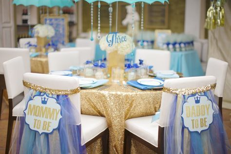 Mommy to Be and Daddy to Be chair back signs for baby shower. Gold glittered La Tavola Linen sequin tablecloth. Blue white and gold baby shower decor. Baby shower ideas. Fancy baby shower with umbrella centerpieces. Umbrella theme. | Lovelyfest Event Design | Royal Blue Baby Shower