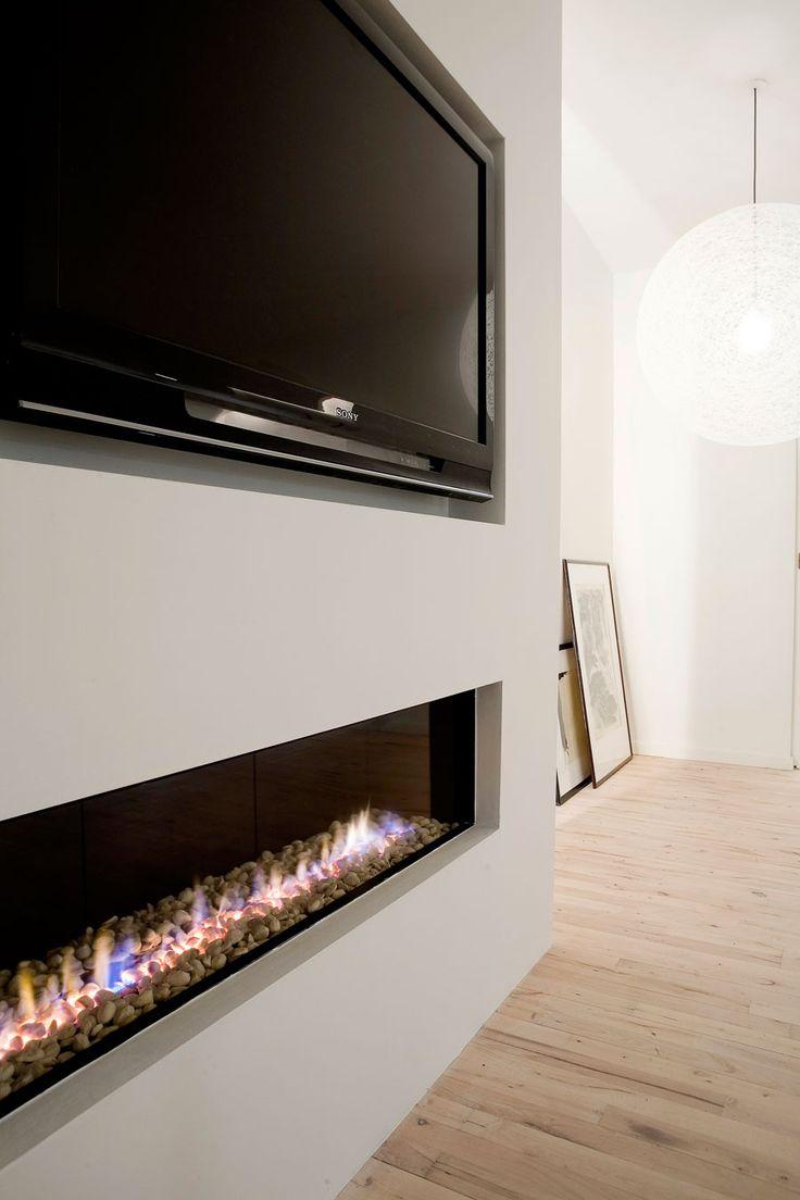 Poner una pared falsa con el cableado por detrás y en la parte de abajo poner un cajón oculto en donde va la chimenea para guardar cosas de la tv
