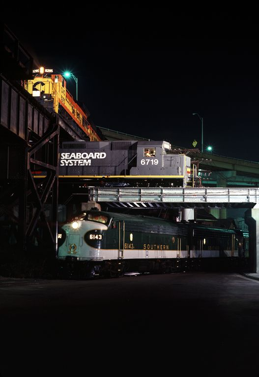 "One of the most ambitious of the night photo sessions occurred at the NRHS Convention in Richmond, Virginia, in 1983. Richmond has the only ""triple crossing"" of three main line railroads in North America; at the time there was the Southern Railway at ground level, with Seaboard System above it and Chessie System above them all. It was arranged for all three railroads to provide locomotives and short trains and the NRHS staff lit the entire scene for about 100 photographers."