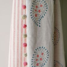 A curtain in our gorgeous new Salcombe Blue Malathi Linen, backed with Rose / Ivory Stripe and finished with pom pom trim. The colours of summer for your home all year round. Perfect for little girls bedroom.