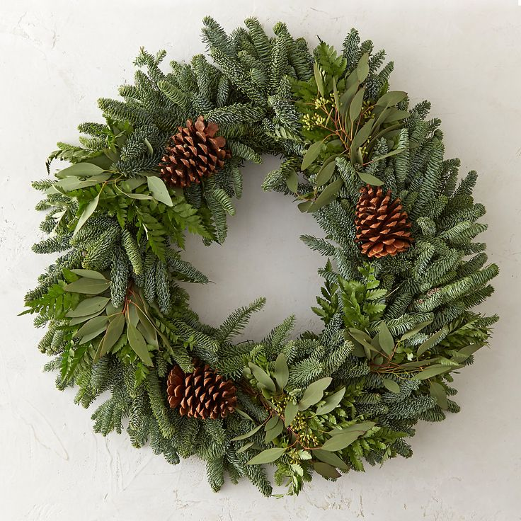 A unique and beautiful accent for the holiday entry, this hand-crafted wreath blends fresh noble fir with seeded eucalyptus, fern fronds, and pine cones