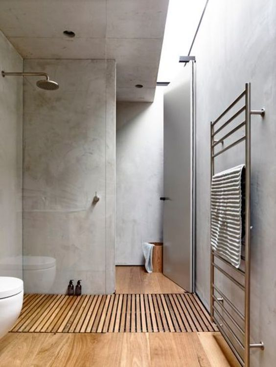 This beautiful wooden floor and built in showerdrainage have probably been made with heavy-duty teak or bamboo flooring, known for their water-resistant properties. The key to maintenance is to oil it all regularly and not leave standing water; underfloor heating would be good with this setup.