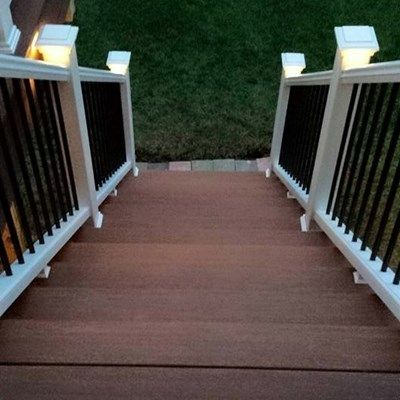 The decking choice here is the brand new for 2015 and gorgeous AZEK Vintage collection in two different colors: Mahogany for the picture frame border, stairs and trim; and Cypress for the decking in the field. The railings are TREX Transcends in white with black, round aluminum balusters for better visibility. The railings also have the way cool TREX lighting system on the post caps. Another WONDERFUL Outdoor Living Space!