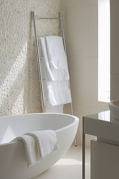 White pebble wall and freestanding bath. https://www.pebbletileshop.com/products/White-Pebble-Tile.html#.VgwIoBFViko