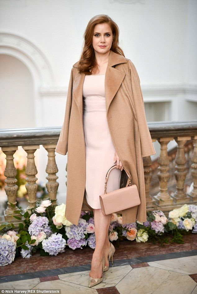 In the nude! Amy, 40, was the epitome of chic elegance in a nude figure-hugging dress, teamed with tonal accessories and a camel coloured coat draped over her shoulders