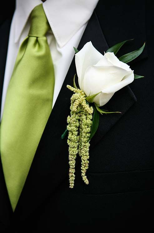 A leaf and sprigs of herbs in different shades of green enhance the white rose of this groomsmans boutonniere.
