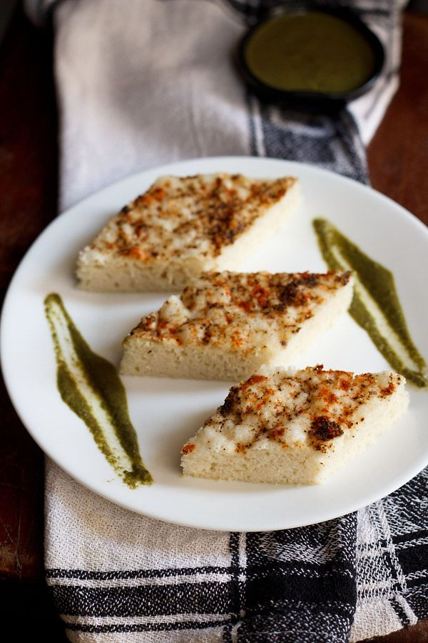 khatta dhokla or white dhokla – fermented and steamed sour cakes made from rice, black gram & sour yogurt, which are light and spongy. mildly spiced with ginger and green chilies.  #dhokla