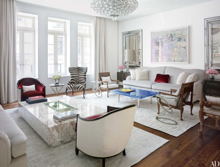 Architect Frederic Schwartz and designers Tony Ingrao and Randy Kemper collaborated with Donny Deutsch to renovate his 1889 Manhattan townhouse. In the living room, a George Condo painting is displayed above a custom-made sofa, one of a pair upholstered in a J. Robert Scott silk mohair. Next to the Venfield zebra chair is a gueridon by Hervé Van der Straeten; the curtains were made using the reverse side of a Kravet fabric, and the cowhide rugs are from Stark Carpet.