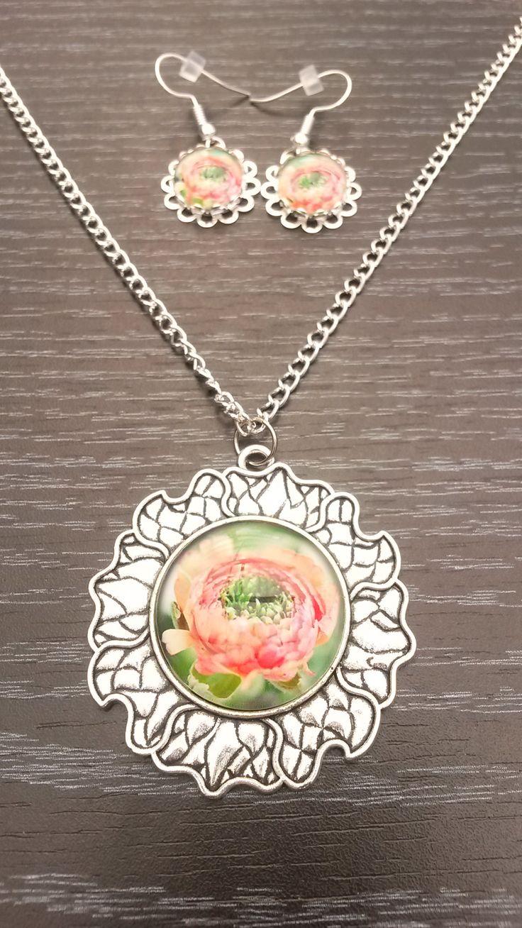 Halsketting met medaillon in de vorm van een bloem en een koraalkleurige bloem als foto, met bijpassende oorbellen.