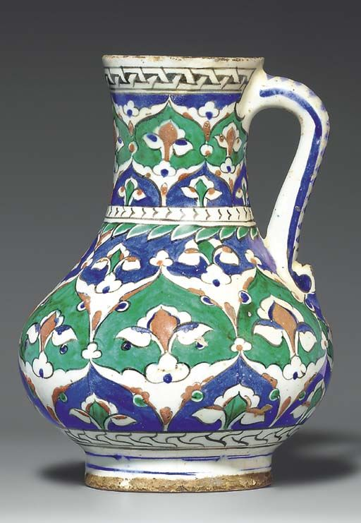 AN IZNIK POTTERY JUG OTTOMAN TURKEY, CIRCA 1585 Of bulbous form on short foot, with slightly flairing mouth and simple loop handle, decorated in green, cobalt-blue and bole-red with black outlines, with dense design of split-palmettes forming lattice with vegetal motifs filling the interstices reserved on green and blue grounds, the base with band of stylized marbling, the waist with simple plait and green foliate fringing, the mouth with band of chain-motif, 9in. (22.5cm.) high