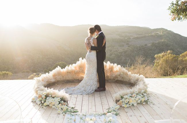 The ceremony area is created from white, pink, and plum flowers and arranged as a circular pampas grass altar