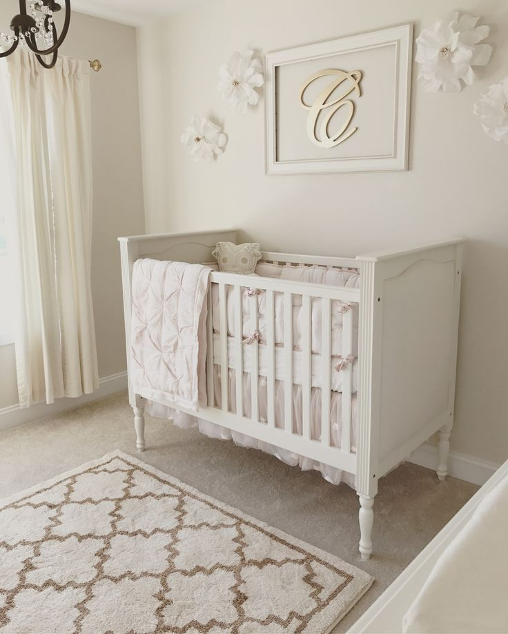Neutral white, gold, and blush pink nursery. Baby. Baby girl. Gold chandelier. Pottery barn Kendall crib. White crib. Crepe paper flowers. Butterfly ethereal bedding. Paper flowers. Framed monogram. Framed initials. Quatrefoil rug. White curtains. Gold curtain rod. Bright. Airy.