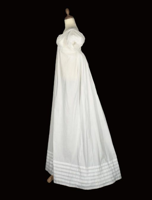Lot 119 - A FINE WHITE MUSLIN GOWN, CIRCA 1800-1810  simple flat-front gown with short, puffed sleeves, very high waist and double drawstring closure at back centre, the only decoration consisting of several bands of tucks to the hem - Christies