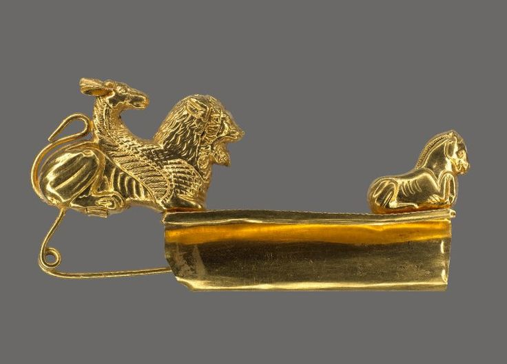 Gold fibula with a bow in the form of a winged Chimaera decorated at the tail with granulation; the oblong catch-plate is decorated with corded lines and a figure of a horse lying down with its forelegs bent up; the pin has a spring of two spiral coils.  525BC-500BC