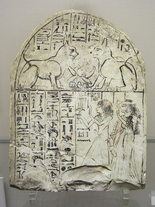 Stele (stone slab) w/ adoration of the Cat of the Re and the Great Cat. Dier el-Medina, Dynasty 19.  Dier el-Medina is an ancient Egyptian village which was home to the artisans who worked on the tombs in the Valley of the Kings during dynasties 18-20 of the New Kingdom period.