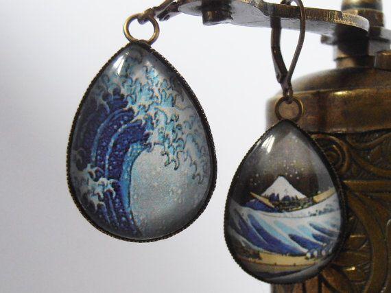"""Hokusai - Bateaux luttant contre les vagues. Boucles d'oreilles en métal de couleur bronze, serties d'un cabochon bombé en verre, mesurant 25 mm x 18 mm. Dimensions de la boucle : 30 mm x 19 mm. """"La grande vague de Kanagawa"""" est certainement l'estampe la plus connue du maître japonais Hokusai (1740-1849). Il a inspiré nombreux artistes européens et est considéré comme le père du Manga, mot qu'il a inventé et qui signifie à peu près « esquisse spontanée ». Photographie © Maní"""