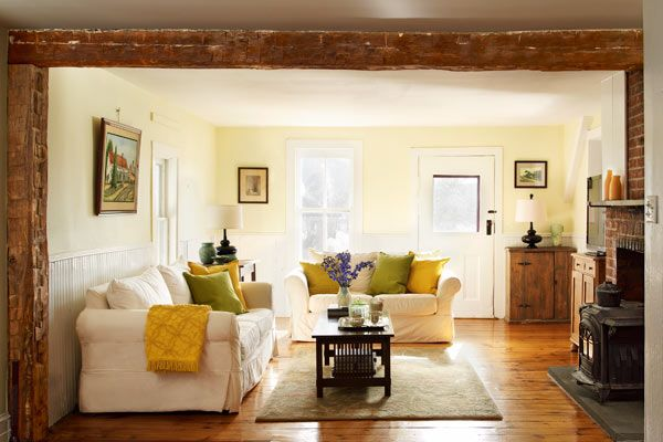 """This farmhouse family room features wainscoting from the early 1900s. The exposed beams were added during a mid-20th-century """"update."""" 