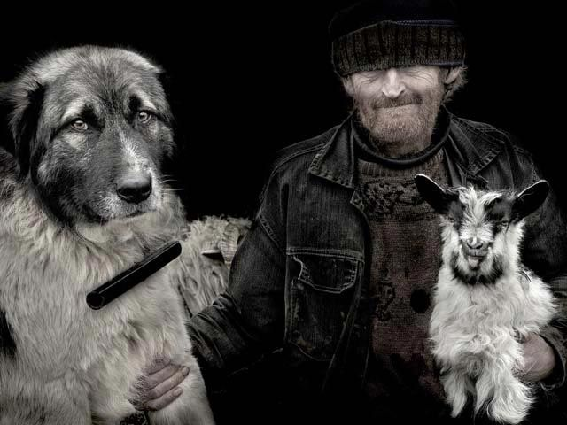 """Friends: Isrvan Kerekes, Ungheria, Menzione d'onore.  """"Ho fatto questa foto in un piccolo villaggio tra i monti Rodnei, in Romania. In questa regione si seguono ancora le antiche tradizioni e la principale attività degli uomini è la pastorizia, l'allevamento di pecore per la produzione di lana e formaggi. Il past re della foto è Pavel, ritratto con il suo inseparabile cane Mutu e la piccola capra a cui Pavel ha dato il nome di Ileana""""."""