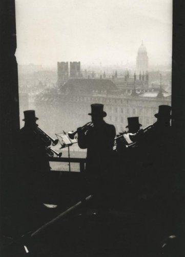 Onbekend | Silhouet van vier mannen met hoge hoeden die met blaasmuziek het Nieuwe Jaar inluiden vanaf de Domtoren in Berlijn. Op de achtergrond daken en kerktorens van de stad. Berlijn, [1931].
