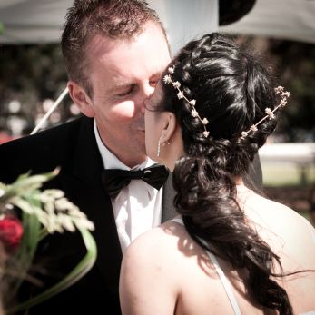 Pat & Bruce | Auckland Photographer Anaïs Chaine Wedding. Beautiful little white flowers on hair and plate style. The Yes kiss! In Mission Bay, Auckland, New Zeland.