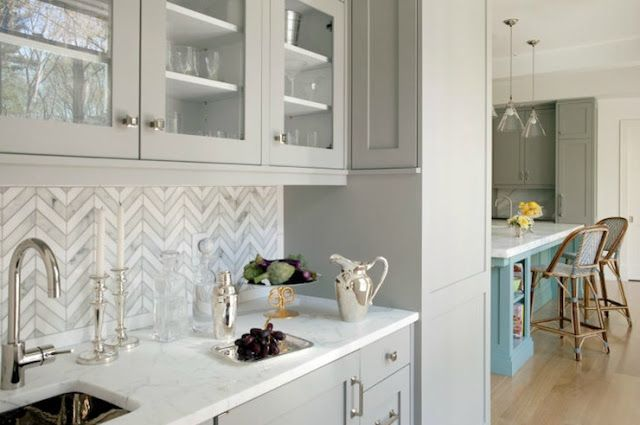 Marble-tiled chevron backsplash with pale gray cabinets