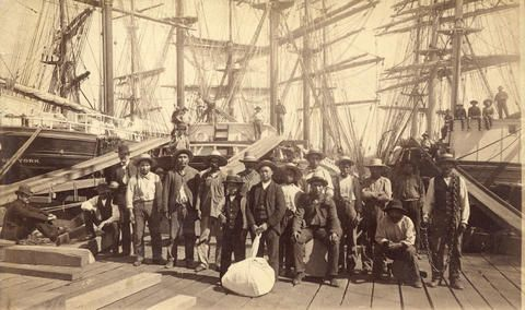 [William Nahanee with a group of longshoremen on the dock of Moodyville Sawmill] - City of Vancouver Archives