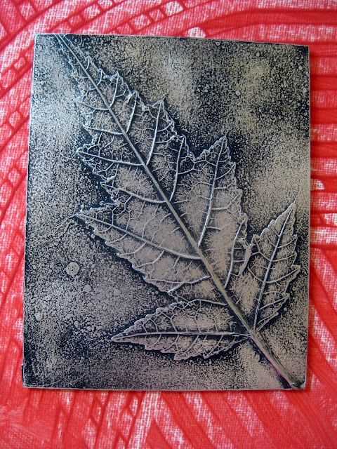 Gather Autumn leaves, grasses, etc. Spray glue to adhere foliage to cardboard or canvas board. Cover with cheap foil gluing flaps that wrap around.  Spray with cheapest black spray paint. Polish off paint with very fine steel wool.