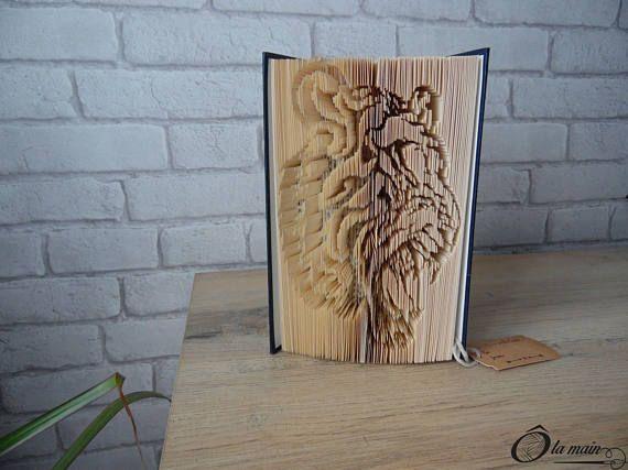 La collection A Livre Ouvert est une série de livres doccasion transformés en objets de décoration via plusieurs techniques (découpage, pliage ou décou-pliage). Chaque page est découpée et/ou pliée à la main pour donner vie à un motif.  Le modèle Loeil du Tigre est un livre découpé et plié pour représenter une tête de tigre. Le livre possède une magnifique couverture bleue et or. VENDU SEUL