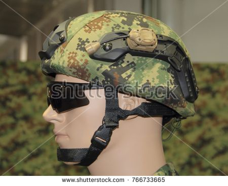Green-brown camouflage military combat helmet with headset and glasses.