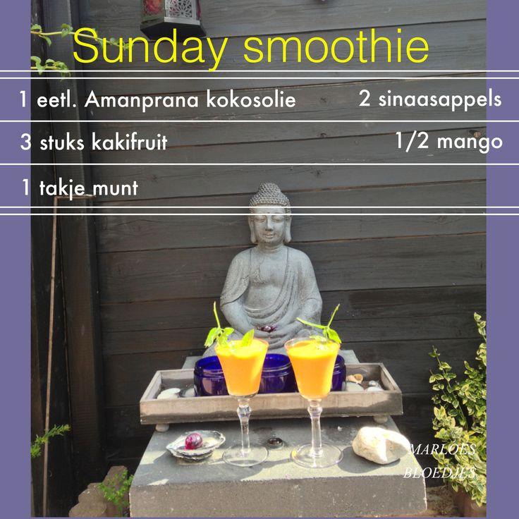 Sunday smoothie met mango, kaki fruit, sinaasappel, een takje munt en Amanprana kokosolie