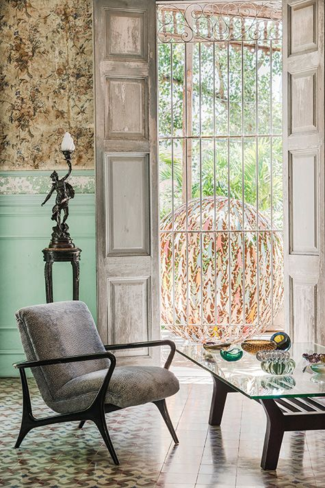 Havana, Cuba - Aquiles and Ruiz's living room  features vintage furniture and a turn-of-the-century light fixture. The original wallpaper is exposed above the painted wainscoting. One of Aquiles's metal spheres is visible through the window.